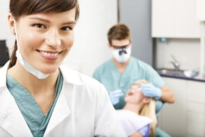 A dentist works on a patient in the background while his dental assistant smiles