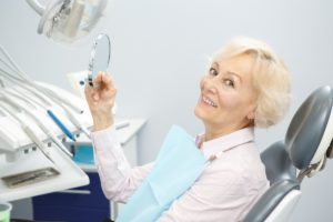 A patient at Cobblestone Park Family Dentistry admiring her smile while sitting in a dental chair